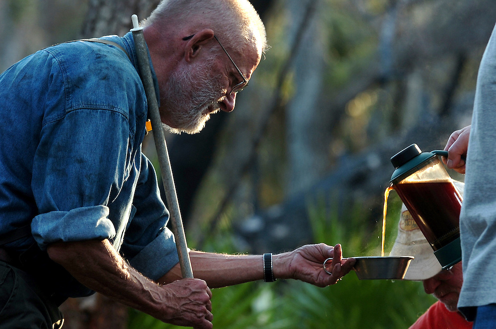 """11/13/07--OCALA--Mac Whitmore (not pictured) pours coffee for John Mennell, 71, of Daytona Beach, before the F-Troop group heads out for another day clearing the Florida National Scenic Trail in the Juniper Prairie Wilderness Area of Ocala Tuesday, Nov. 13. Mennell a former prosecutor had double knee surgery a few months ago, but couldn't stay away from the trail. """"I'm not going to let this thing slow me down,"""" Mennell said. """"Some people play golf I like to work. The stress out here it's physical exhertion and serenity, the peace that I have for so long searched for.""""  Photo by Julie Busch Branaman"""