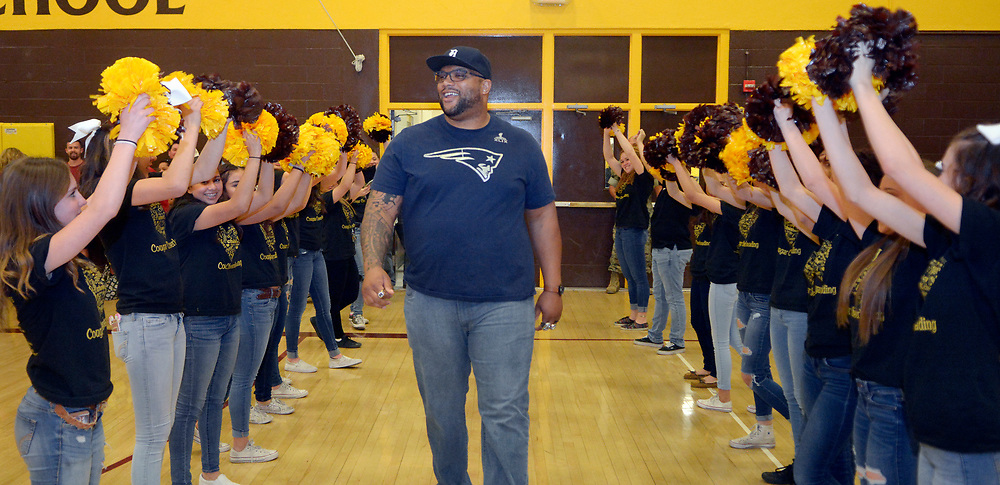 gbs050417j/SPORTS -- Former Cibola football player and current New England Patriots and Super Bowl Champion, Alan Branch, enters the Cibola gym through cheerleader pom poms during a program honoring him at Cibola on Wednesday, May 3, 2017. (Greg Sorber/Albuquerque Journal)