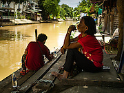 07 SEPTEMBER 2016 - BANGKOK, THAILAND: People relax on the canal bank in the Pom Mahakan community.  Forty-four families still live in the Pom Mahakan Fort community. The city of Bangkok has given them provisional permission to stay, but city officials say the permission could be rescinded and the city go ahead with the evictions. The residents of the historic fort have barricaded most of the gates into the fort and are joined every day by community activists from around Bangkok who support their efforts to stay.      PHOTO BY JACK KURTZ