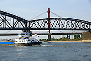 A barge passes under a bridge on the river Rhine near Arnhem, Nederland