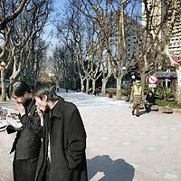 China,Shanghai ,maart 2008..Rokende krantenlezende Chinese jongeren in 1 van de parken van Shanghai.