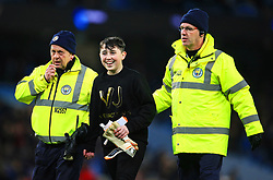 A young fan is escorted off the pitch by stewards after receiving the goalkeeping gloves of Argentina's Willy Caballero - Mandatory by-line: Matt McNulty/JMP - 23/03/2018 - FOOTBALL - Etihad Stadium - Manchester, England - Argentina v Italy - International Friendly