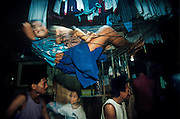 Young girl and a baby swing ina a hamock in a gold miner's familly's cramped and overcrowded living conditions at their ballmill in Mount Diwata, Mindanao, The Philippines.