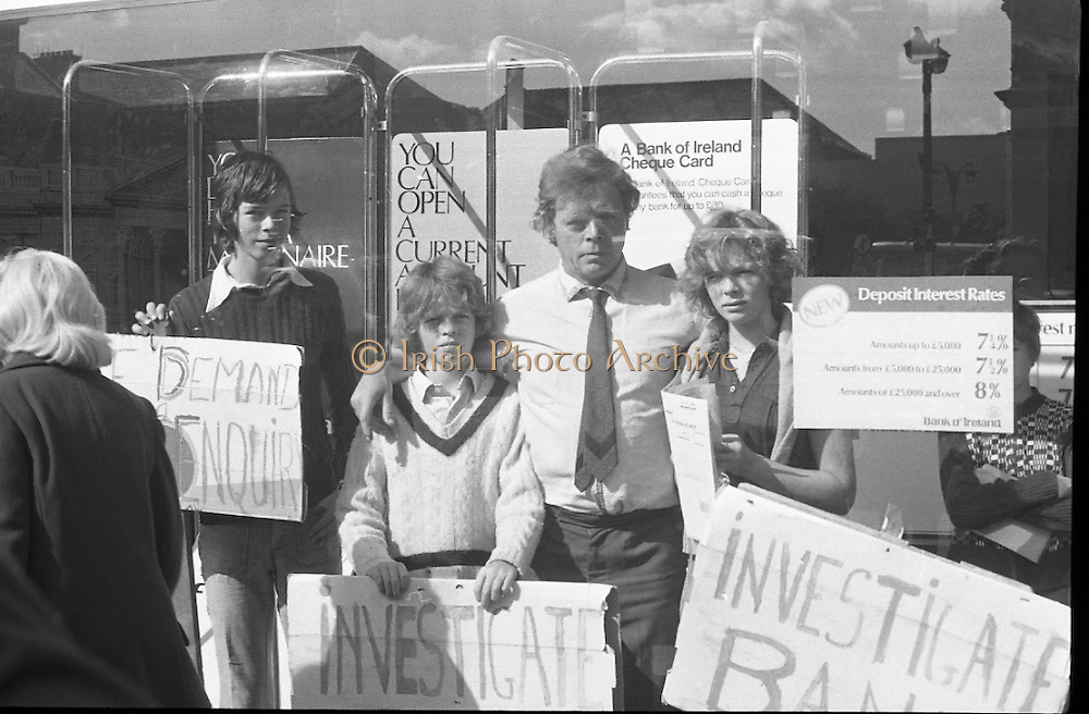 Fergus Rowan sits in at Bank of Ireland.  (J70)..1975..22.08.1975..08.22.1975..22nd August 1975..As a result of the 1970 bank strike which lasted for six months, the Rowan family business found itself in financial difficulties. During the strike the Rowans had had to accept cheques in good faith in order to stay in business. When the cheques came for settlement the bank refused as they stated that some were 'dodgy'. This put severe strain on the business which was eventually put into receivership.As part of the process the Rowan business beside the bank was put up for sale and was purchased by B.o I. Rowan was outraged and started a campaign against the bank which culminated in a sit in at the banks headquarters in Westmoreland St,Dublin. He also became a thorn in the side of the bank at the A.G.Ms raising many points...Fergus Rowan defiantly poses in the bank window accompanied by his family,