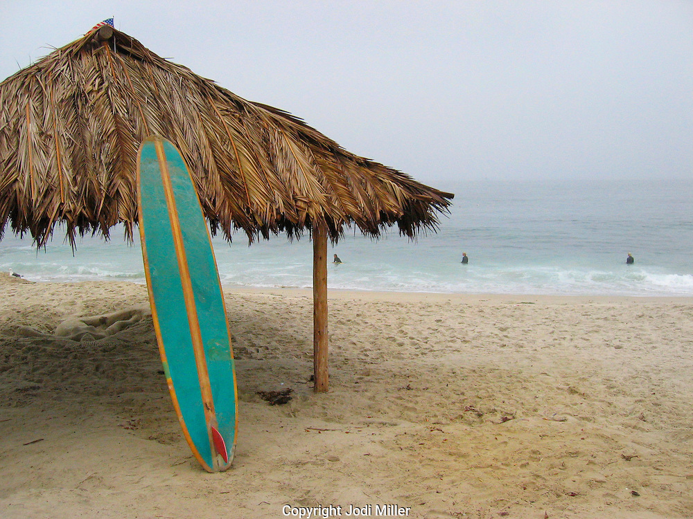 A surfboard leaning against a grass hut in La Jolla CA.