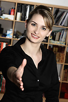 cute and smiling businesswoman at the office desk inviting you to shake her hand