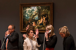 "© Licensed to London News Pictures. 07/12/2016. London, UK. Sotheby's staff make bids on behalf of telephone clients in front of ""Venus and Adonis resting in an extensive landscape, with Cupid and hunting dogs and their quarries"" by Cornelis Cornelisz. Van Haarlem Roelandt Savery Haarlem which sold for a hammer price of GBP150k (est. 150-200k) at the Old Masters Evening Sale at Sotheby's in New Bond Street. Photo credit : Stephen Chung/LNP"