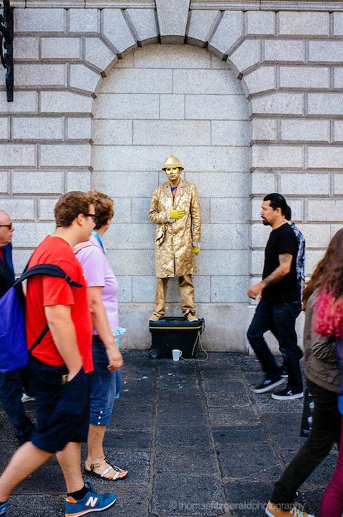 A street performer wearing a gold coat and mask, performs on the streets of Dublin City, Ireland, as people walk two and fro
