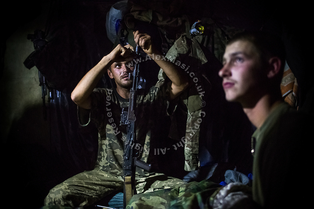 A soldier living in an underground bunker near the trenches is cleaning up his rifle at night, on the frontline of Hranitne, near Mariupol, southeast Ukraine.