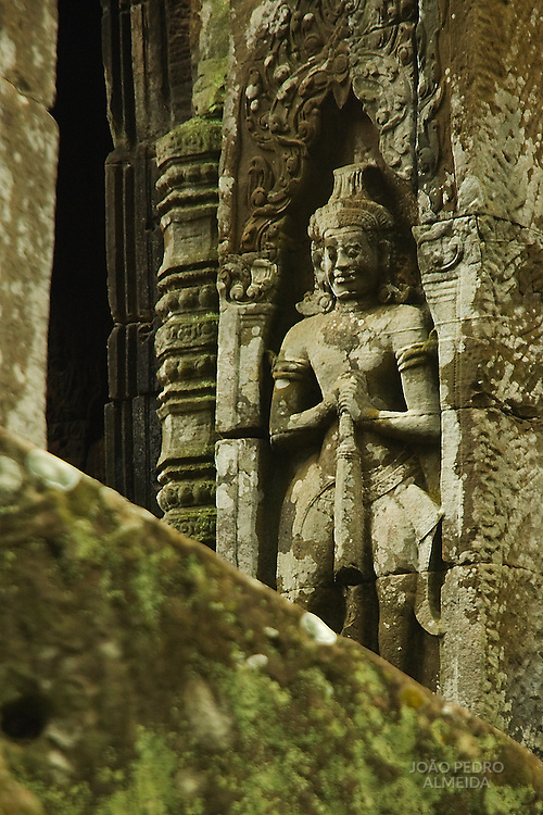 Statue at the walls of one of Angkor's temples