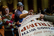 Supporters of Businessman and 2016 Republican presidential candidate, Donald Trump, reach for signs as they prepare to listen to Tump participate in a Q&A format event with Liberty University President, Jerry Falwell, Jr  during a campaign event at the Adler Theater in Davenport, IA on January 30, 2016. Trump is in Iowa campaigning in the final days before the Iowa Caucus.<br />
