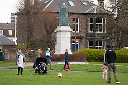 Edinburgh, Scotland, UK. 31 March, 2020. Police patrol public parks and walking areas to enforce the coronavirus lockdown regulations about being outdoor. Family outside in Victoria Park playing football. Iain Masterton/Alamy Live News