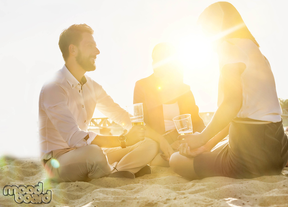 Business people celebrating success while drinking beer on the beach with lens flare in background