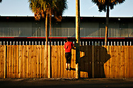 MELISSA LYTTLE   |   Times<br /> SP_345156_LYTT_MOTEL_7 (November 22, 2011, St. Petersburg, FL) Christopher &quot;C.J.&quot; Stone Jr., 15, jumps to see over the privacy fence erected on the northside of the Mosley Motel, and into the parking lot of the neighboring Economy Inn Stadium Motel, where his mom had gone to look for him when he disappeared for a few minutes. As C.J.'s mom tried to reneter the Mosley, the clerk at the front desk stopped her, saying she was seen on the security camera slipping into the Economy Inn, so it was assumed it was for a drug deal. The Mosley has taken great measures to clean up their act, reduce the number of police calls and to separate themselves from the Economy Inn, where drugs and prostitutes run rampant. [MELISSA LYTTLE, Times]