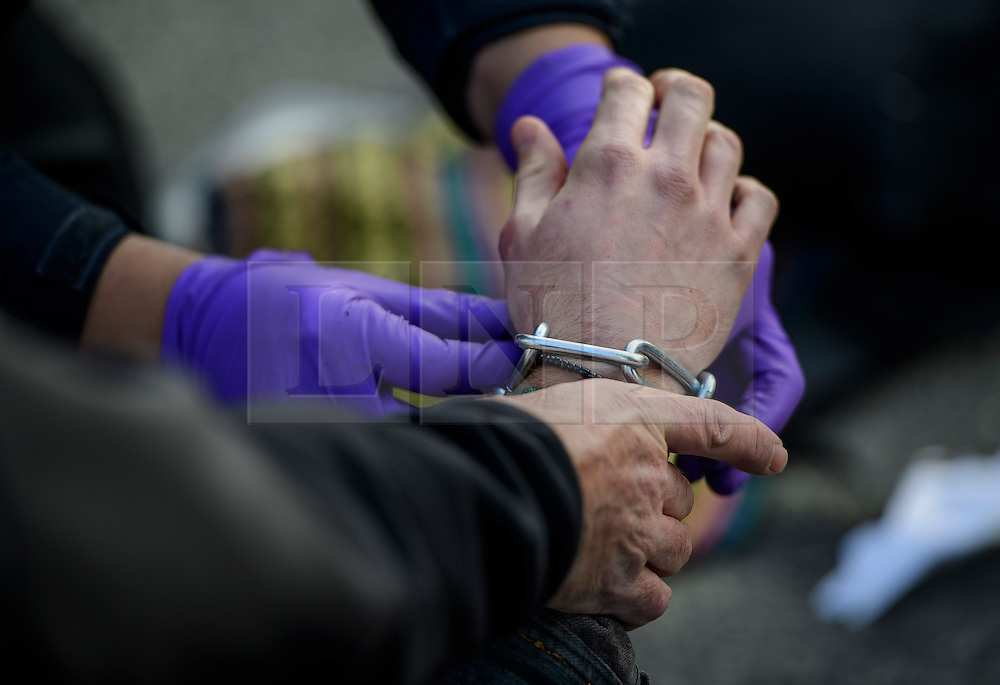 "© Licensed to London News Pictures. 19/11/2016. Heathrow, UK. A chain on an activists hand, used to attach him to the road. A group of activists stage attach themselves to a road surrounding  Heathrow Airport, during a demonstration against the expansion of Heathrow Airport and the building of a third runway. Some activists  threatened ""direct action"". Photo credit: Ben Cawthra/LNP"