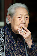 Traditional Sanjing Hutong (old quarter). Old lady with cigarette.