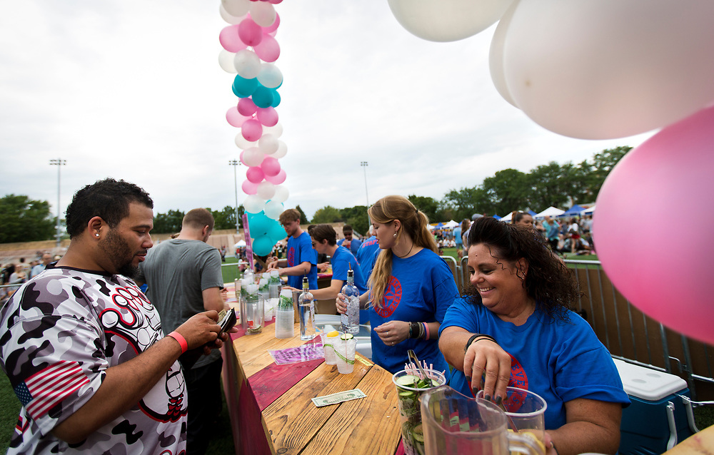 Mary Rieder, right, serves a drink from the Death's Door Spirits cocktail lounge during the 4th annual Yum Yum Fest held at Breese Stevens Field, Sunday, August 6, 2017.