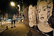 Two girls heading to a club in the Meatpacking, passing by two giant artworks representing Madonna, New York.
