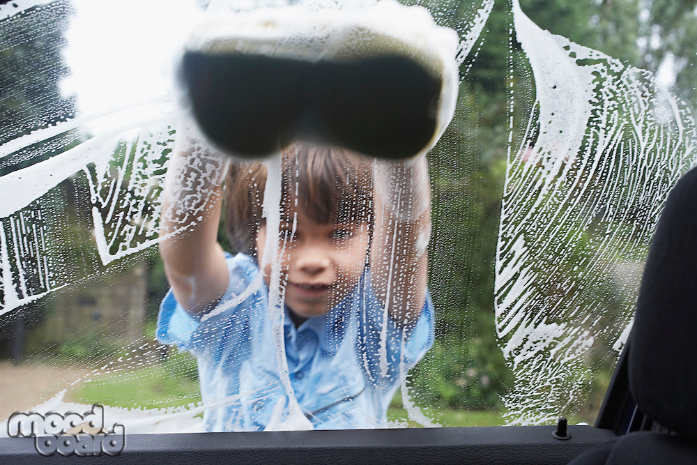 Young boy (7-9) washing car with sponge view from inside car