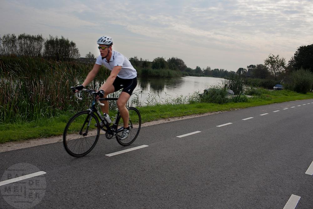 Een wielrenner fietst op de racefiets langs de Amstel.<br /> <br /> Cyclists are riding nearby the Amstel