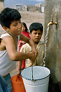 Children getting water at public tap at a shanty town which are called pueblos jovenes on the outskirts of Lima, Peru.