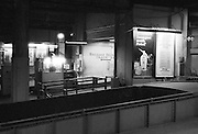 End of a track at Grand Central creating a sense of isolation and abandonment. Noir effect. Several well-lit posters and ads provide life to the photograph.
