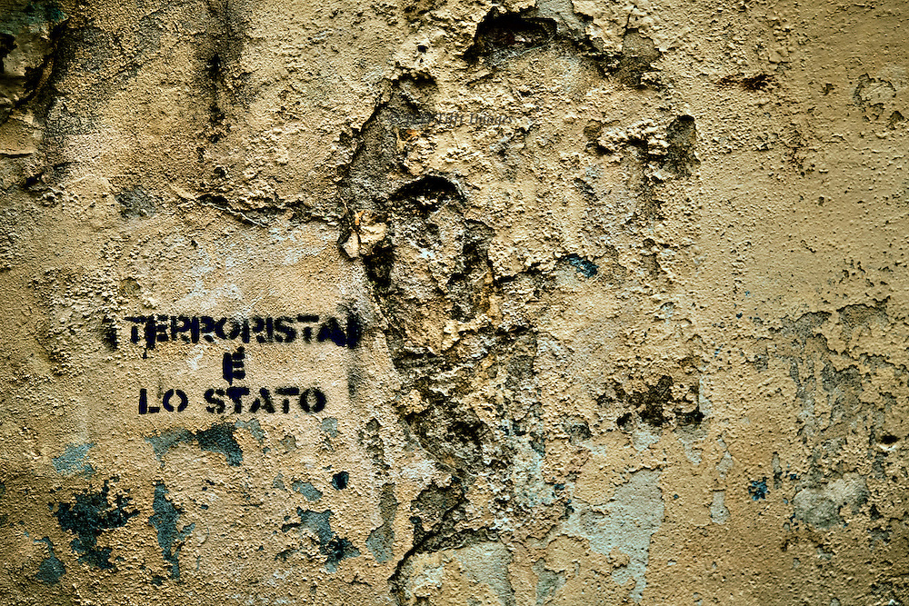 "I like to collect pictures of wall signs and graffiti that have some relevance to their location.  Or some mystery.  Here the message on a scruffy old wall is: ""Terrorista e lo stato"" painted in black, apparently through a template."