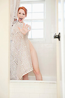 Portrait of an excited young woman standing in bathtub