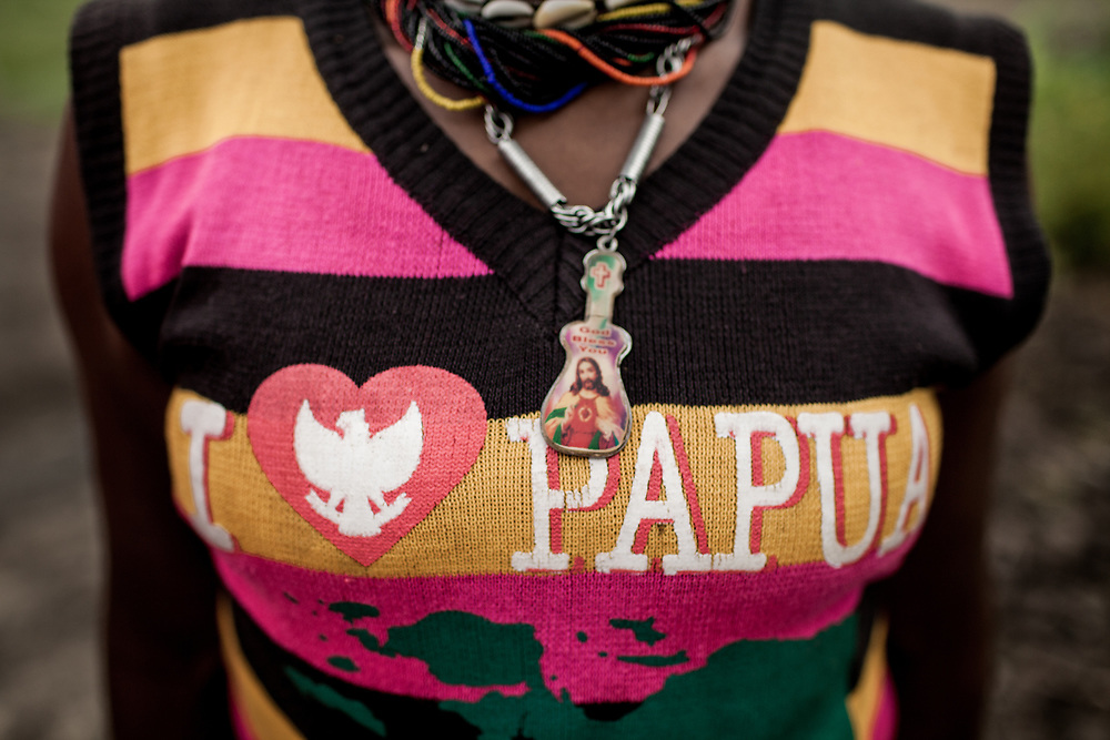 "A young mother with HIV is seen wearing a necklace with a picture of Jesus Christ and a sweater that reads, ""I love Papua."""