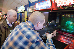 Two friends playing shooting games in the amusement arcade whilst on a day trip to Skegness organised by Nottingham Disabled Friendship Club,