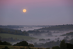 © Licensed to London News Pictures. 28/09/2015. Dorking, UK. The supermoon sets over fog near Box Hill in Surrey.  Photo credit: Peter Macdiarmid/LNP