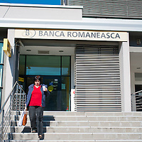 TIMISOARA, ROMANIA - APRIL 21:  A woman walks out of the Banca Romanesca while drinking coffee l on April 21, 2013 in Timisoara, Romania.  Romania has abandoned a target deadline of 2015 to switch to the single European currency and will now submit to the European Commission a programme on progress towards the adoption of the Euro, which for the first time will not have a target date. (Photo by Marco Secchi/Getty Images)
