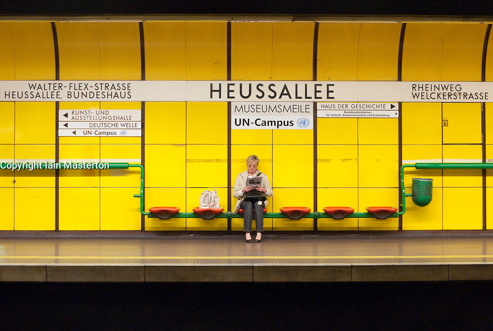 Woman waiting for train on platform at a station on the Bonn subway in Germany