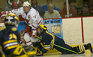 2/18/06  Omaha, Ne University of Nebraska at Omaha Scott Parse, No. 23, keeps his eyes on goalie University of MIchigan  Noah Ruden as Jason Dest falls down.v Saturday night at the Omaha Civic Auditorium..(Photo by Chris Machian/Prarie Pixel Group).