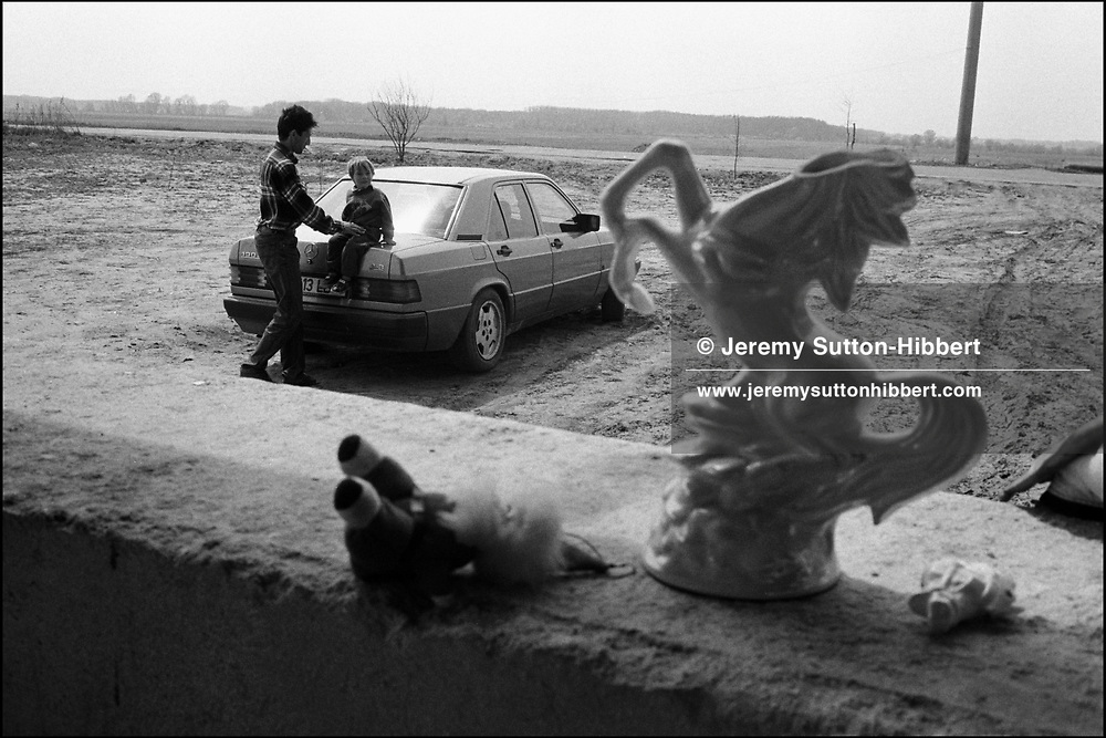 Puia Stanescu sits his son on top of his Mercedes Benz car, in front of his new home, in the Kalderash camp of Sintesti, near Bucharest. In the foreground lies broken an ornament of a horse, the once favoured method of transport with the Roma community.
