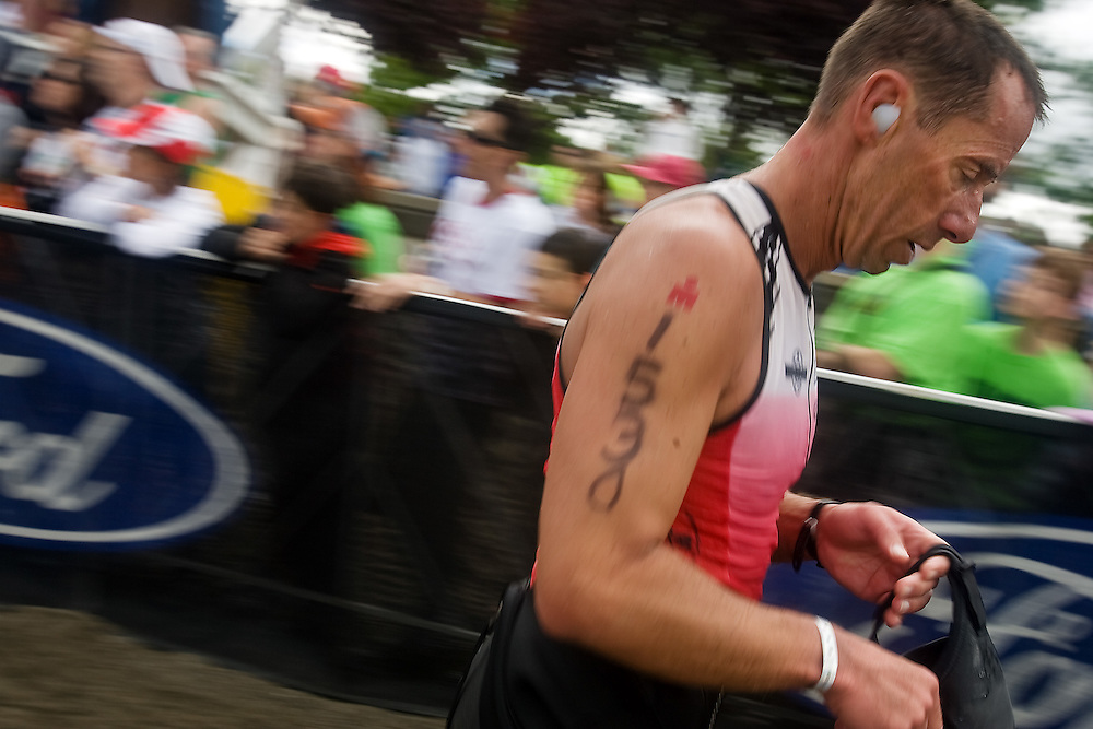 JEROME A. POLLOS/Press..Jeffrey Miller, from Hayden, makes his way toward the transition area after exiting the water following the 2.4-mile swim Sunday at the Ford Ironman Coeur d'Alene.