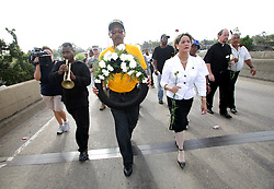 29 August 2006. New Orleans, Louisiana. Lower 9th ward. Great Flood commemoration and memorial ceremony; to 'honor and remember our loved ones who have passed. <br /> L/R; Renowned jazz trumpeter Marlon Jordan, Clarence Bickham (with wreath) and local council woman Cynthia Willard Lewis lead the march as people prepare to pay tribute to and salute the victims of hurricane Katrina, which struck one year ago today.<br /> Photo Credit©; Charlie Varley/varleypix.com