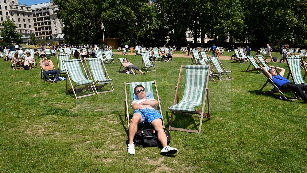 © Licensed to London News Pictures. 27/06/2019. LONDON, UK.  People relax on deckchairs in the warm temperatures and sunshine in Green Park during lunchtime.  The forecast is for temperatures above 30C on Saturday.  Photo credit: Stephen Chung/LNP