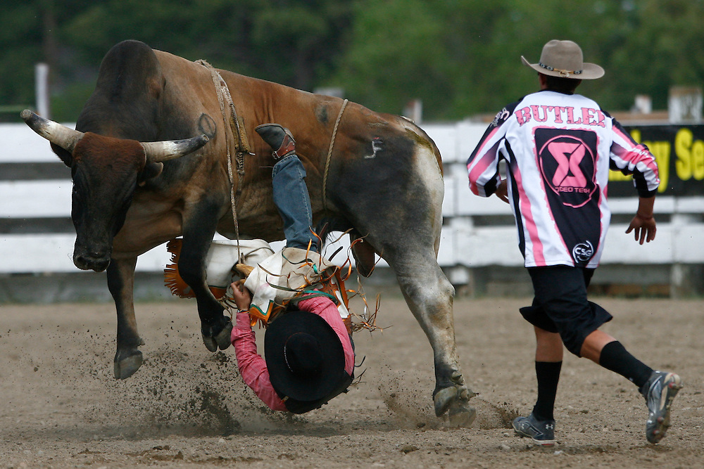 061811-Evergreen, COLORADO-evergreenrodeo-Bull fighter Joe Butler rushes in to help free bull rider Cody Samora, of Cortez, CO, during the Evergreen Rodeo Saturday, June 18, 2011 at the El Pinal Rodeo Grounds..Photo By Matthew Jonas/Evergreen Newspapers/Photo Editor