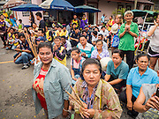 "23 JUNE 2015 - MAHACHAI, SAMUT SAKHON, THAILAND: People kneel in the street and pray during the City Pillar Shrine Procession in Mahachai. The Chaopho Lak Mueang Procession (City Pillar Shrine Procession) is a religious festival that takes place in June in front of city hall in Mahachai. The ""Chaopho Lak Mueang"" is  placed on a fishing boat and taken across the Tha Chin River from Talat Maha Chai to Tha Chalom in the area of Wat Suwannaram and then paraded through the community before returning to the temple in Mahachai.   PHOTO BY JACK KURTZ"