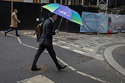 A businessman strides through rain under a large brolly on Lime Street in the City of London, the capital's financial district, 7th March 2018, in London England.