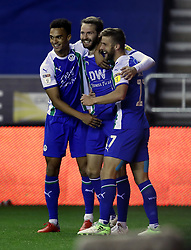 Wigan Athletic's Nick Powell (centre) celebrates scoring his side's first goal of the game with Michael Jacobs (right) during the Sky Bet Championship match at the DW Stadium, Wigan.