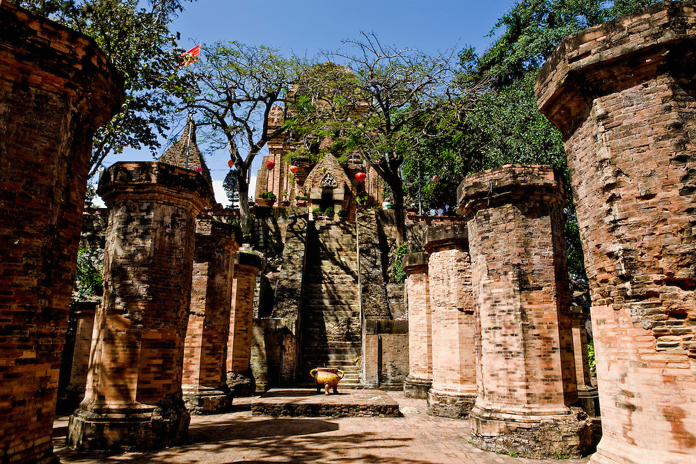Po Nagar temple site.  Brick pillars of the reception hall, its wooden ceiling vanished, march symmetrically toward the steep stair up to the tmeple area on the hill above.  The structures have recently been repaired and stabilized.