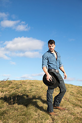 handsome cowboy on a grassy hillside
