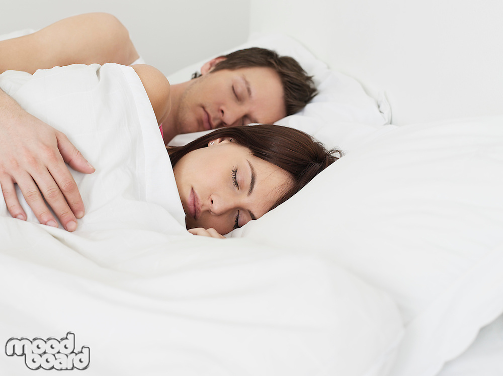 Young couple sleeping in bed man's arm around woman