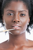 Close-up portrait of young woman applying lip gloss with brush