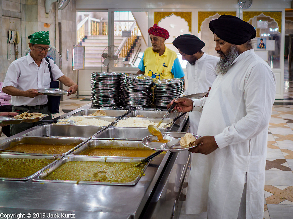"""25 FEBRUARY 2019 - BANGKOK, THAILAND: Sikh and Thai men gets their meal during the morning """"Langar"""" (communal meal) at the Gurdwara Siri Guru Singh Sabha. The Gurdwara serves about 500 free meals Monday through Saturday and about 1,000 free meals on Sundays. The meals are free for anyone who walks into the Gurdwara, regardless of their religion or nationality. Although Sikhs are not vegetarians, the Langar meals are vegetarian so anyone can them without violating a religious edict on diet. The Gurdwara Siri Guru Singh Sabha in Bangkok is one of the largest Sikh Gurdwaras (temples) outside of India. It is in Bangkok's """"Little India"""" neighborhood, next to Chinatown. Construction on the Gurdwara started in 1979 and finished in 1981.     PHOTO BY JACK KURTZ"""