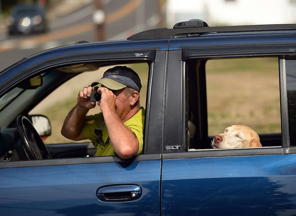 7/25/16 :: REGION :: STAND ALONE :: A passing motorist stops and snaps a photo as workers from Stamford Wrecking tear-down St. Michael The Archangel Roman Catholic Church on Liberty St. in Pawcatuck Monday, July 25, 2016. The church has been closed since April of 2012 when structural problems were found. The new church will be built on the original foundation. (Sean D. Elliot/The Day)