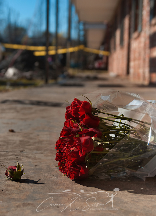 A bouquet of flowers lies on the sidewalk outside an apartment building at Academy Crossing in Starkville, Miss., where an early morning fire took the lives of nine people, including six children, Dec. 28, 2009. Oktibbeha County coroner Mike Hunt said the children ranged in age from four months to six years old. The cause of the fire is still under investigation. (Photo by Carmen K. Sisson/Cloudybright)