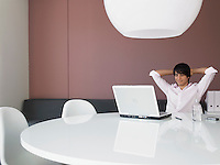 Relaxed Businessman Using Laptop in Modern Office